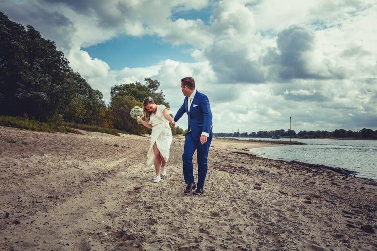 Bruidspaar op Waal strandje gemaakt door De bruidsfotograaf uit Den Bosch ('s-Hertogenbosch) en omgeving.